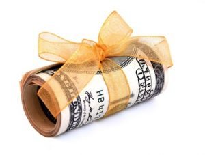 Money roll wrapped in a golden ribbon with a bow on top